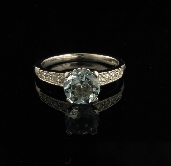1 x Custom made 18ct White gold Aquamarine and Diamond Engagement Ring.  Band bead set with round brilliant cut diamonds.  The ring features a millgrained finish.