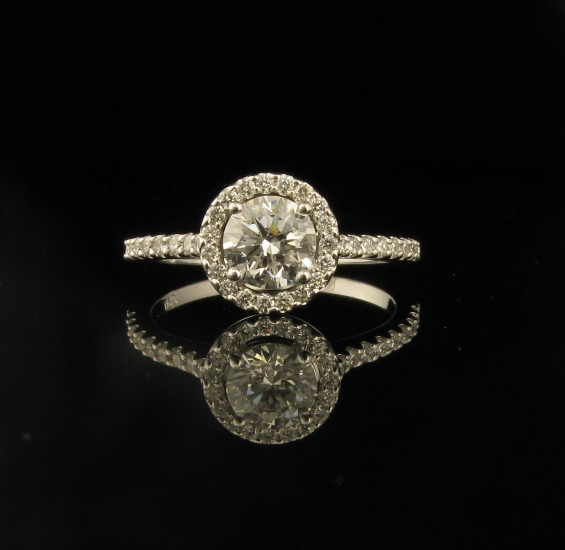 18ct White gold Diamond Engagement Ring.  18ct White gold four claw setting.  Set with 1 x .60 ct round brilliant cut F SI1 Diamond.  GIA Certified  and  laser inscribed.  Claw set around the diamond in a halo setting and claw set diamonds in the shoulders.