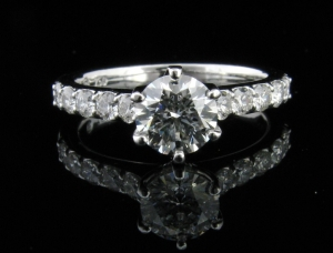18ct White Gold Diamond Engagement Ring. Six claw coronet setting set with .72ct round brilliant cut G SI1 diamond. GIA Certified and laser inscribed. Claw set shoulder diamonds.
